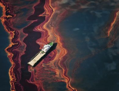 On May 6, 2010, a ship cuts through a band of oil on the surface of the Gulf of Mexico that seeped up from the Deepwater Horizon wellhead. Photo ? Daniel Beltra for Greenpeace.