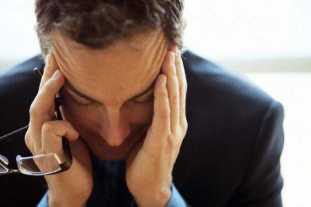 Businessman Holding Head in Hands --- Image by ©LWA-Stephen Welstead/CORBIS